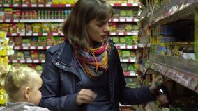 A young woman with a child in a supermarket chooses goods. Mom is driving a little girl on a trolley. Mom and daughter. Choose food. 4K stock video footage