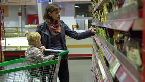A young woman with a child in a supermarket chooses goods. Mom is driving a little girl on a trolley. Mom and daughter. Choose food. 4K stock footage