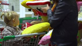 A young woman with a child in a supermarket chooses goods. Mom is driving a little girl on a trolley. Mom and daughter. Are looking at the pillow. 4K stock footage