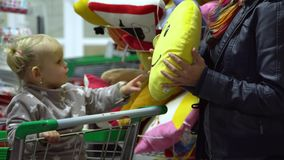A young woman with a child in a supermarket chooses goods. Mom is driving a little girl on a trolley. Mom and daughter. Choose towels. 4K stock footage