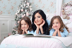 A young woman with children blue knit cardigan in the bed near Christmas tree. The young dark-haired women reading a book two girls of three and five years on Royalty Free Stock Image