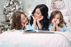 A young woman with children blue knit cardigan in the bed near Christmas tree. The young dark-haired women reading a book two girls of three and five years on Stock Photo