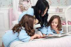 A young woman with children blue knit cardigan in the bed near Christmas wreath. The young dark-haired women reading a book two girls of three and five years on Royalty Free Stock Photo