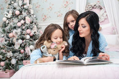 A young woman with children blue knit cardigan in the bedroom near the Christmas tree. The young dark-haired women reading a book two girls of three and five Stock Photo