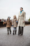 Young woman with children in warm clothing walking together on street Stock Images