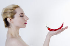 Young woman with chili pepper. Young beautiful woman with chili pepper on her hand royalty free stock photos
