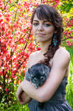 Young woman with chinchilla. Pretty young woman model with bright colorful makeup wearing summer dress, blue earrings, holding her pet chinchilla on her hands Royalty Free Stock Photography