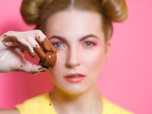 Young woman with chocolate in her fingers. Portrait of cute attractive blonde young woman with chocolate in her fingers Stock Photo