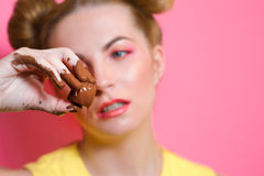 Young woman with chocolate in her fingers. Portrait of cute attractive blonde young woman with chocolate in her fingers Stock Photography