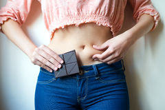 Young woman with chocolate showing her fat Stock Images