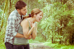 Young woman choking with man standing behind performing heimlich maneuver, park environment and casual clothes Stock Image