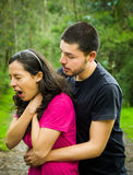 Young woman choking with man standing behind performing heimlich maneuver, park environment and casual clothes Royalty Free Stock Photos