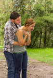 Young woman choking with man standing behind performing heimlich maneuver, park environment and casual clothes Royalty Free Stock Photography