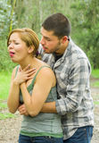 Young woman choking with man standing behind performing heimlich maneuver, park environment and casual clothes Royalty Free Stock Photo