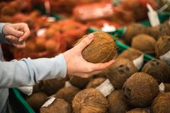 Young woman choose fresh coconut at supermarket. stock photos