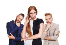 Young woman choose from two men, isolated. Love triangle. Young beautiful women choose from to handsome men isolated at white. Hard choice, lover, husband royalty free stock photography