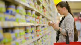 Young woman chooses baby food in the supermarket, Mother chooses food for their child in the market, girl stands near. The supermarket shelf and selects the stock footage