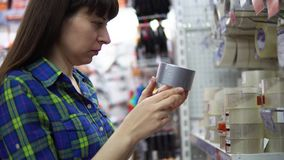 A young woman chooses and buys a gray metalized adhesive tape in the supermarket. A young woman in a blue checkered shirt chooses and buys a gray metalized stock video footage