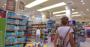 A young woman chooses and buys products and goods in a supermarket