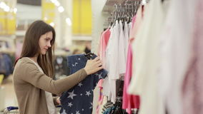 Young woman chooses clothes for a child stock video footage