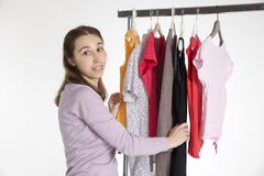 Young woman chooses clothes, isolated on white. Young woman chooses clothes on , isolated on coat rack white background Royalty Free Stock Photos