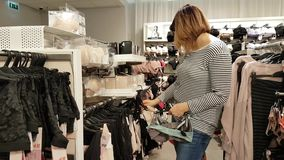 Young woman chooses clothes stock video
