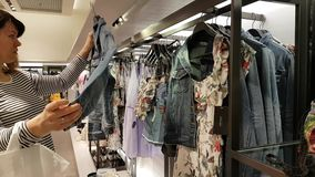 Young woman chooses clothes stock video footage