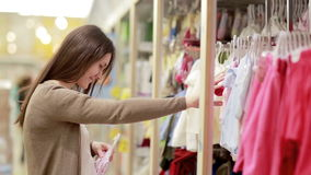 Young woman chooses clothes for newborn baby