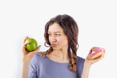 Young woman chooses between a donut and an apple. Concept of healthy nutrition and diet stock photo
