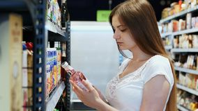 Young woman chooses drink in the Supermarket, customer selects product on the shelves in the store stock video