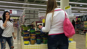 Young woman chooses a flower pot in a supermarket. In the background a woman eating ice cream. stock video