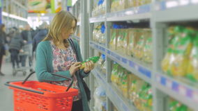 Young woman chooses food in the supermarket, Mother chooses food for their child in the market, girl stands near the. Young woman chooses food in the supermarket stock video