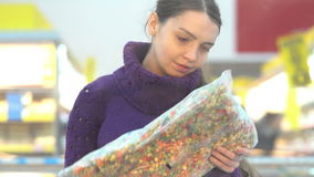 Young woman chooses frozen vegetables in the supermarket stock video footage