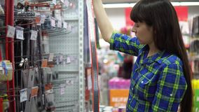 A young woman chooses a large iron ruler with an angle in the supermarket. A young woman in a blue checkered shirt chooses and buys a large iron ruler with an stock video footage