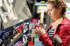 Young woman chooses lipstick in shop. Royalty Free Stock Photography