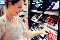 Young woman chooses lipstick in store Royalty Free Stock Photography