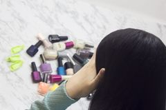 Young woman chooses nail polishes, beauty and fashion, difficulty of choice, dilemma, Spa salon at home stock photography