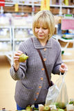 Young woman chooses pears in store Stock Image