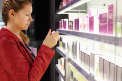 Young woman chooses perfume in shop. Stock Photos
