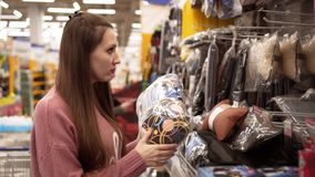 A young woman chooses a pillow for a car in a supermarket stock video footage