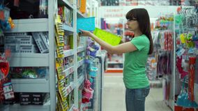 Young woman chooses small plastic basket in store. stock video