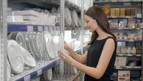 Young woman chooses plates in shop cookware, dish choosing by elegant girl in supermarket Royalty Free Stock Photos