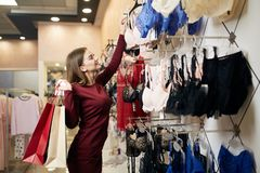 Young woman chooses brassiere among set in a boutique. Pretty girl considers bra with shopping bags in her hand in. Underwear store. Consumerism concept royalty free stock photo
