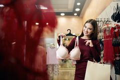 Young woman chooses brassiere among set in a boutique. Pretty girl considers bra with shopping bags in her hand in. Underwear store. Consumerism concept royalty free stock photos