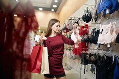 Young woman chooses brassiere among set in a boutique. Pretty girl considers bra with shopping bags in her hand in. Underwear store. Consumerism concept royalty free stock photography