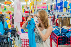 Young woman chooses shirt in shop royalty free stock images
