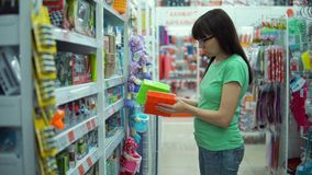 Young woman chooses small plastic basket in store. stock video footage