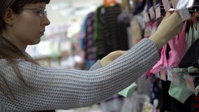 A young woman chooses socks in a clothing department in a supermarket. A young woman chooses socks in a clothing department in a store. Shopping in store or stock video