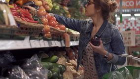 Young woman chooses vegetable eggplant in the big store stock footage