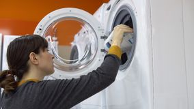 A young woman chooses a washing machine in a home appliance store. A young woman in a gray cardigan choosing washing machine in the shop of household appliances stock video